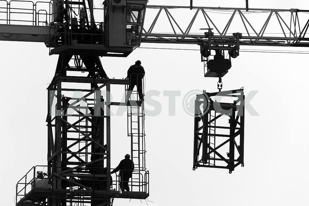 Silhouettes of cranes with a load on the construction of buildin — Image 49987