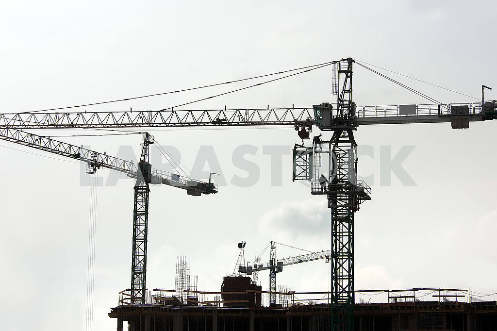 Silhouettes of cranes with a load on the construction of buildin — Image 49988