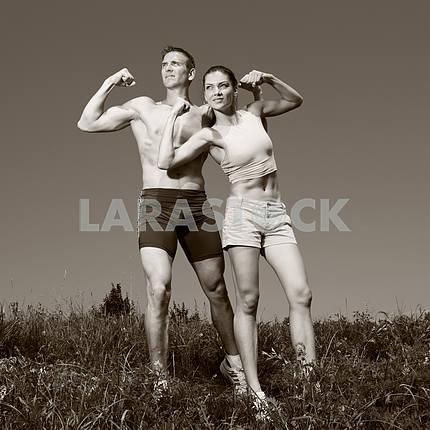 Молодая спортивная пара, улыбаясь в голубое небо