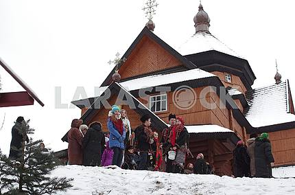 On the Feast of Baptism people, young people in Hutsul clothes on the background of the ancient church in Kryvorivn