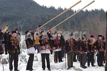 Группа гуцулов с трембитами, бартками, рожками на фоне Карпат на празднике Крещения в Криворивне.