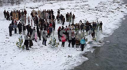 На обледеневшем берегу реки возле креста из льда люди с хоругвами, священнослужители, люди в гуцульской одежде.