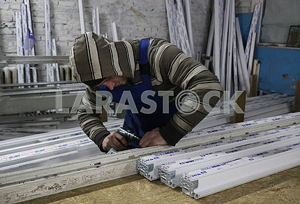 Worker in the shop for the manufacture of windows in Ugledar