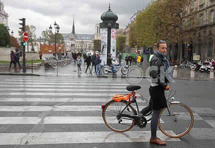 Велосипедистка на пешеходном переходе на парижской улице