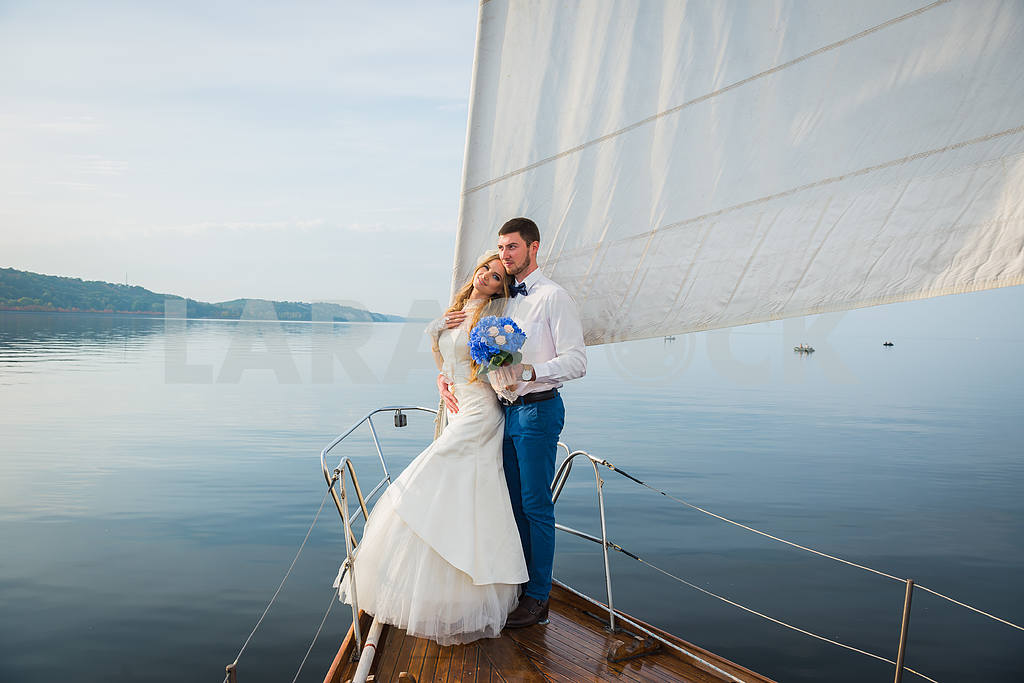 Honeymoon sailing - Stylish young bride and groom standing on the nose of board the sailing yacht — Image 50162