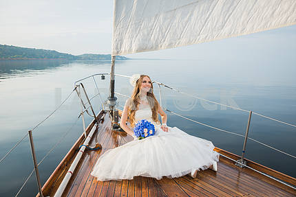 Beautiful blonde bride in a long white dress poses on a sailing yacht at sea with the blue bouquet in her hand and deaming on a sunny day