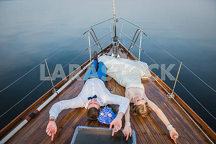 Happy honeymoon sailing - Stylish young bride and groom laying on the wooden board the sailing yacht - happyly lookin into the sky