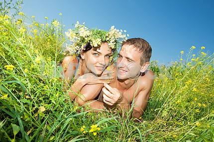 Молодые любви пара, улыбаясь в голубое небо