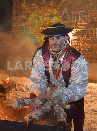 The cook in a pirate suit prepares a shish kebab