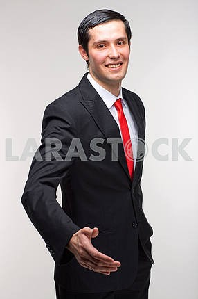 A young representative man in a suit holds out his hand to greet