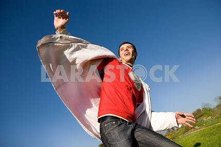 Happy young man flies in blue sky