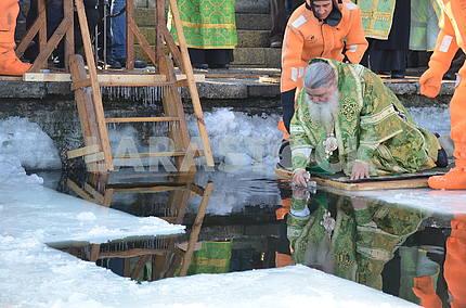 The priest sanctifies the water