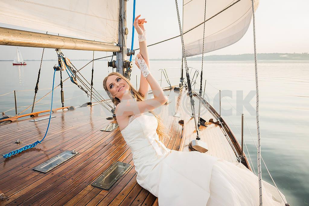 Wedding on a yacht. Beauty bride. Beautiful model girl in white/creamy dress. Female  portrait. Woman posing. Cute lady outdoors. Kyiv sea resrvoir.  wooden yacht evening sun — Image 50507