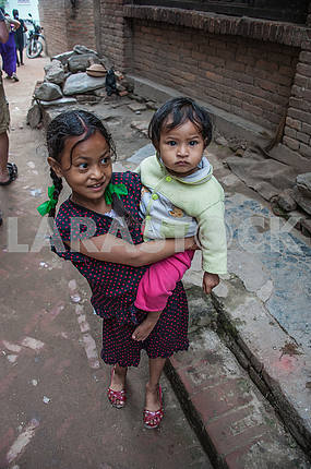 Маленькая девочка несет на руках братика.