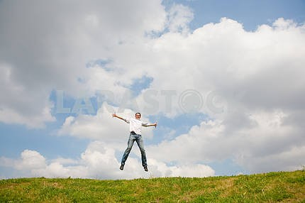 Happy young man - jumping  against backdrop of blue sky.