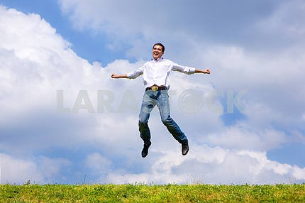 Happy man is jumping on a field