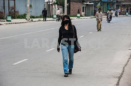 Girl with a dark patch on his face walking down the street