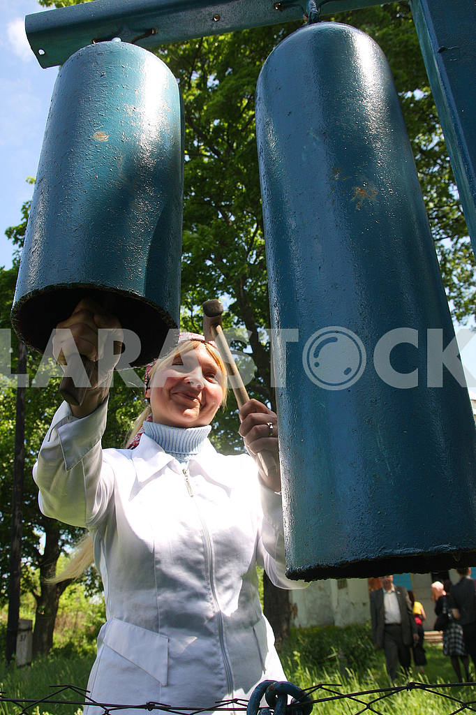 Woman bell ringer hammering on iron cylinders — Image 50845