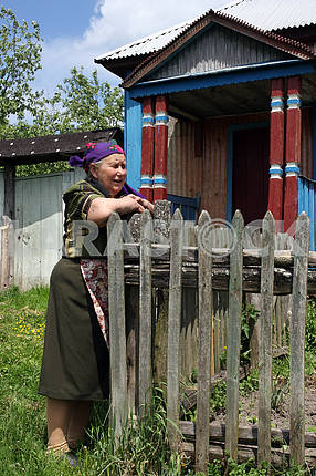 Old woman in the yard of his home
