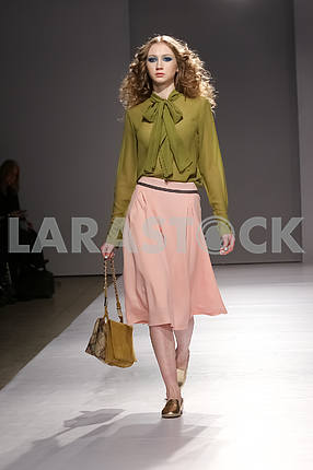 Model in an olive blouse and a padded skirt from Gres