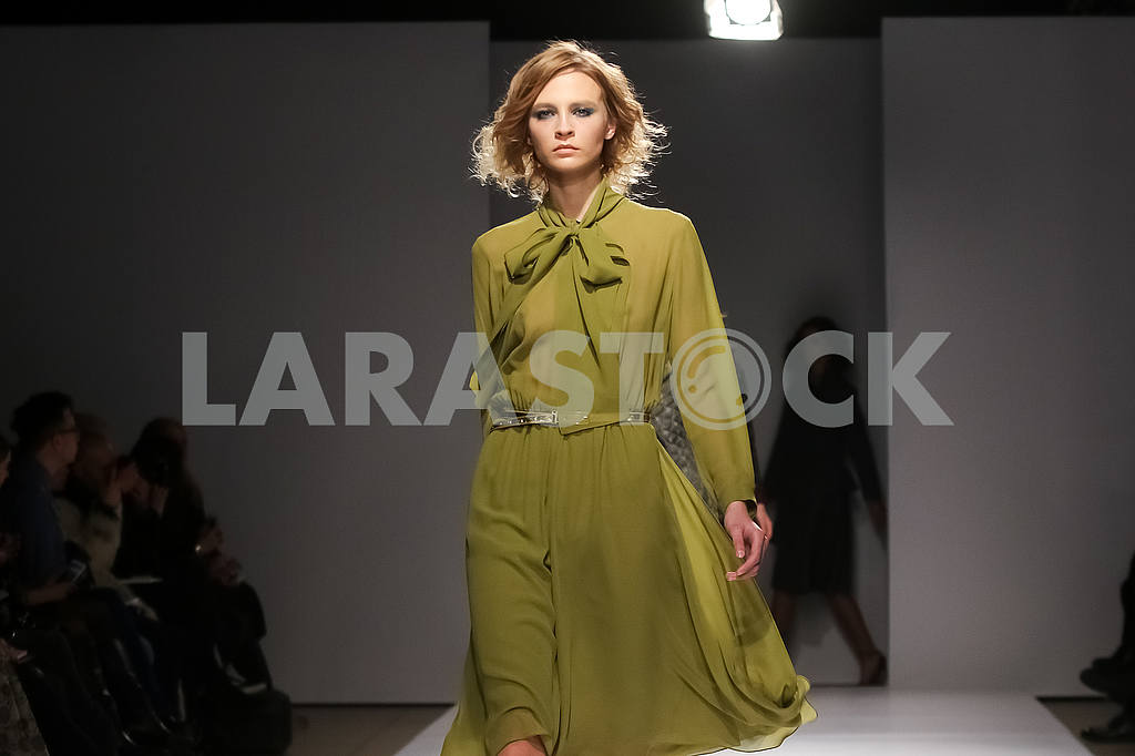A model in an olive dress. Display by V by Gres — Image 51220