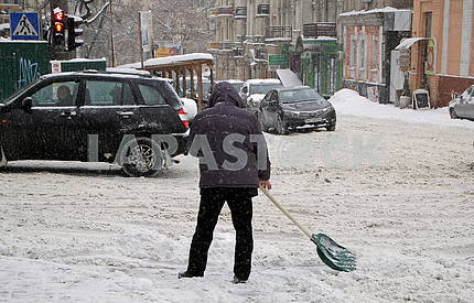 A man is cleaning the snow with a shovel in Kiev