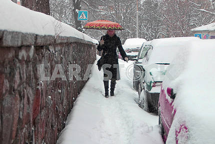 A woman is walking along a snow-covered street in Kiev
