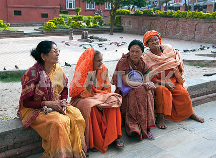 Older women sit waiting for the start of the funeral ceremony