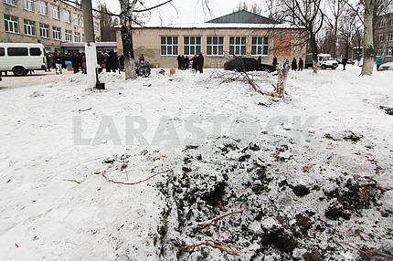 Funnel from an artillery shell near the point of delivery of humanitarian aid in the courtyard of school № 3 in Avdeevka