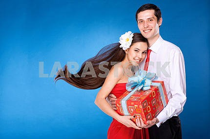 guy with girl are holding box with gift