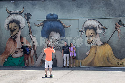 Туристы фотографируются на фоне рисунков . Майами