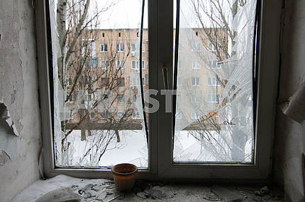 Broken window of the apartment affected by the shelling.