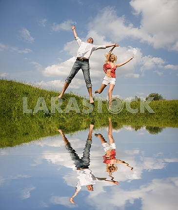Happy Young love Couple - jumping under blue sky