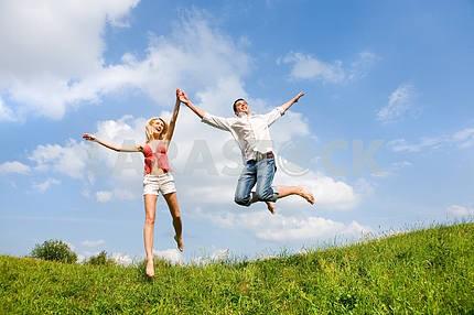 Счастливый молодая пара - прыжки в небо над зеленый луг