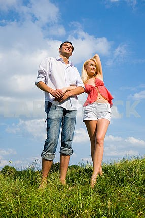 Young couple standing on summer meadow