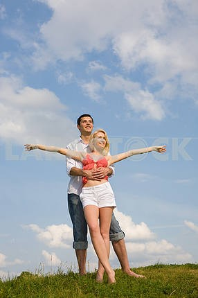Young couple under cloudy sky