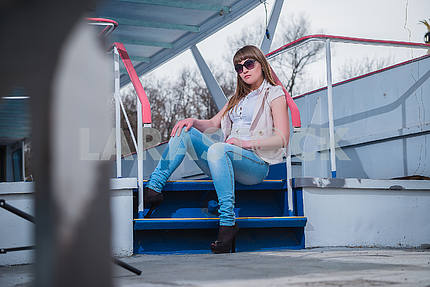 Girl with the light hair sitting on  the stairs, spring, sunny warm day, in sunglasses and blue jeans. resting, looking throuth sunglasses
