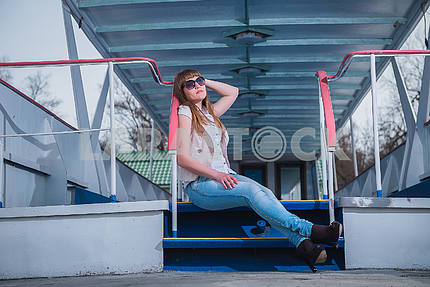Girl with the light hair sitting on  the stairs, spring, sunny warm day, in sunglasses and blue jeans. resting,