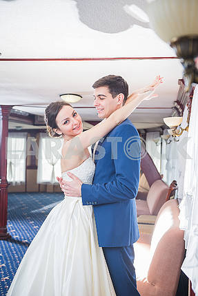 Lovely wedding couple hugging each other. the bride in a white wedding dress smiling happily. groom in a blue costume. looking into each other. couple in love