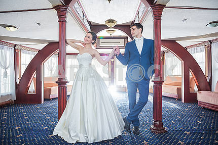 Lovely wedding couple holding each other. the bride in a white wedding dress smiling happily. groom in a blue costume. looking into each other. couple in love