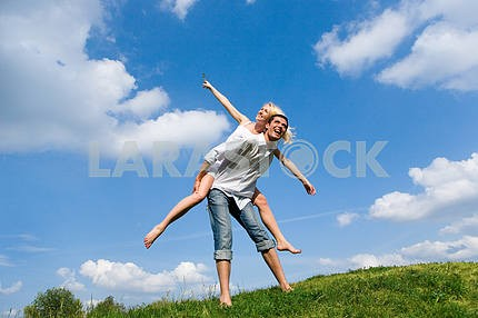 Happy Young Couple - jumping in the sky above a green meadow