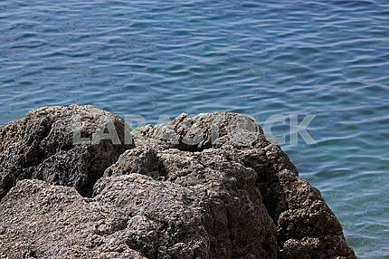Rock on a background of blue water