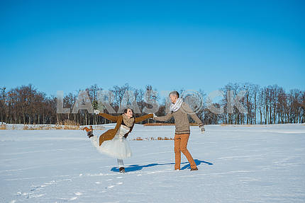 Young wedding couple playing in snow on a sunny winter day. Rustic style wedding. lovely girl in short wedding white dress, blue sky on the background. Brown style wedding. Dancing