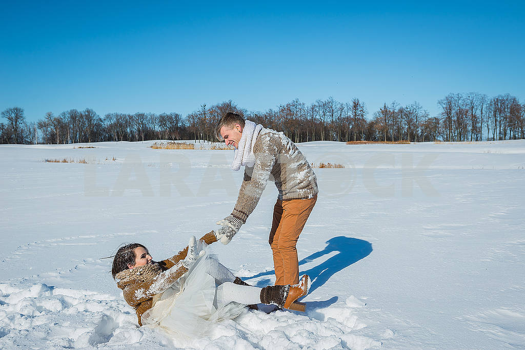 Young wedding couple playing in snow on a sunny winter day. Rustic style wedding. lovely girl in short wedding white dress, blue sky on the background. Brown style wedding. girl fall down into snow — Image 52640