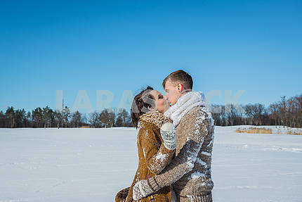 Young wedding couple kissing on the snow field on a sunny winter day. Rustic style wedding. lovely girl in short wedding white dress, blue sky on the background. Brown style wedding