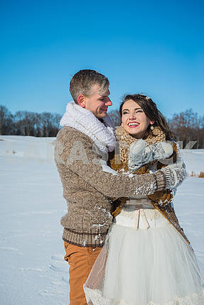 Young wedding couple holding each other on a sunny winter day. Rustic style wedding. lovely girl in short wedding white dress, blue sky on the background. Brown style wedding