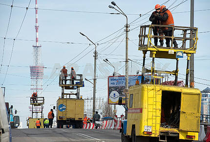 Workers repair the wires of the trolleybus line