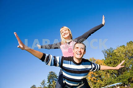 Young love couple smiling end fly under blue sky