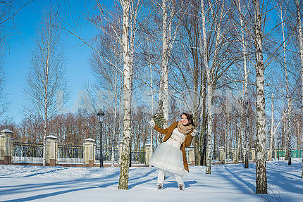 Красивая невеста в солнечный зимний день за березой. Снежная погода. Небо и деревья на заднем плане. Девушка в коротком свадебном платье, деревенском стиле