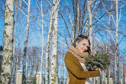 Красивая невеста в солнечный зимний день за березой. Снежная погода. Небо и деревья на заднем плане. Девушка в коротком свадебном платье, деревенском стиле. Улыбающийся портрет